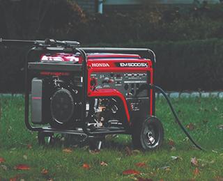 Une génératrice Honda EM5000 rouge sur une pelouse à l'extérieur d'une maison en brique bordée d'arbustes.