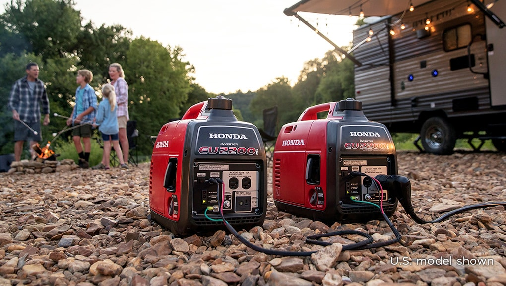 Close up image of generator in foreground with man in wooded campsite in background.