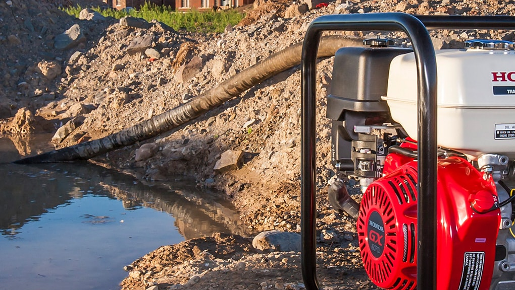Close up of pump in foreground with hose attachment running to water in background