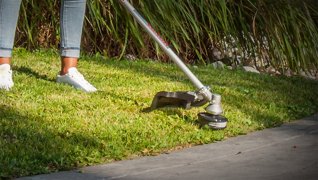 Close up of woman using trimmer on grass along driveway